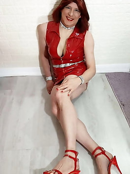 TGirl Lucy shows off her big fake tits in red PVC mini dress